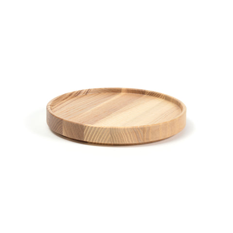 3/4 view of a round wooden tray on a white background. Striations in wood vary from light to medium. Tray has straight sides with a lip protruding above the flat surface..