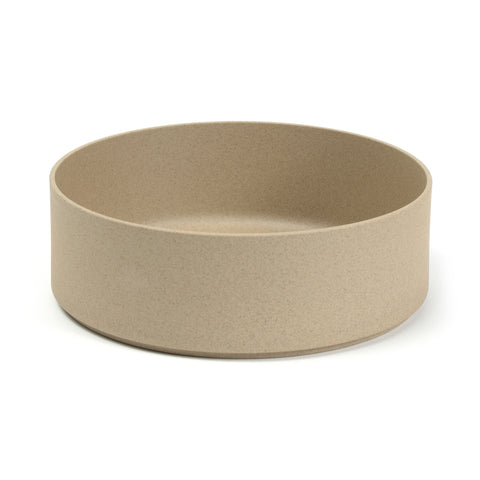 A round minimalist bowl the color and texture of pressed sand, with straight sides, a flat bottom and a wide mouth, positioned in a 3/4 view on a white background.