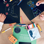 A cropped image of children's hands drawing colorful pictures on sheets of black reusable paper. Wishy Washy colored markers and Butterstix colored chalk are strewn about.