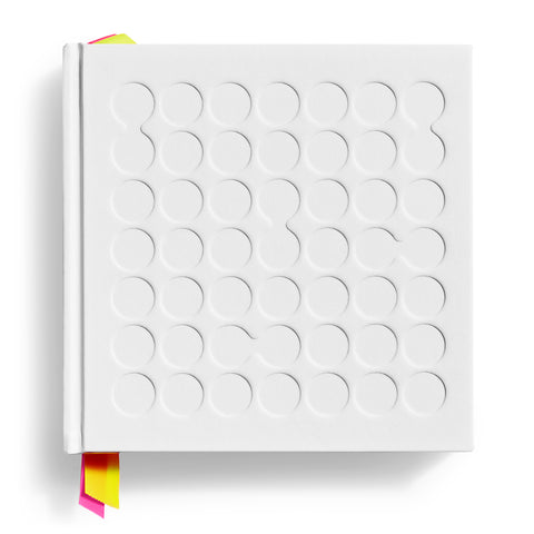 White square book cover with debossed circles, some connected and multicolored ribbons peeking from top and bottom of spine