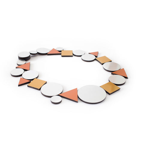Side angle view of a necklace made up of flat, reflective shapes connected directly to each other on a white background. The shapes include silvery disks of several sizes, copper colored triangles, and gold colored squares. The shapes have black edges.