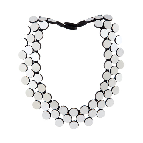 Front view of a necklace made up of three strands of flat, silvery, reflective disks connected directly to each other on a white background. Each disk is black around the edge.