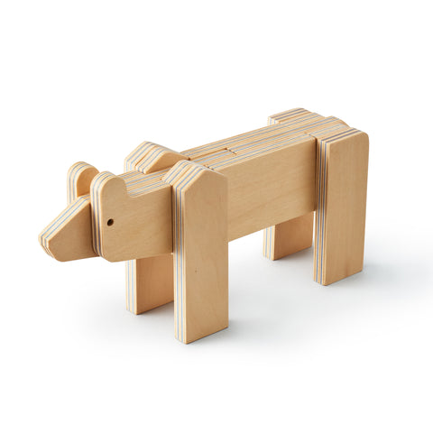 3/4 view of a minimalist bear made up of flat plywood pieces fitted together. The bear is standing on four legs, its' pieces are primarily rectangular with rounded ends for the shoulders, ears, and nose  Lines between plywood layers are blue.