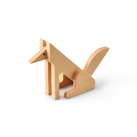 3/4 view of a minimalist fox made up of flat plywood pieces fitted together. The fox is seated on its hind legs, its tail, ears, and nose are sharp and the legs are long with rounded ends. Lines between plywood layers are orange.