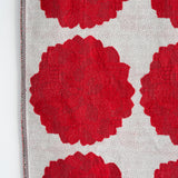 Detail of a Knit Bloom Blanket that is off white showing a pattern of large red dahlias, one wholly, and five partially visible.