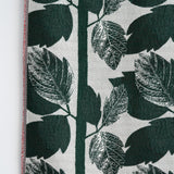 Detail of a Knit Bloom Blanket that is off white with a dark green, vertical leaf pattern.
