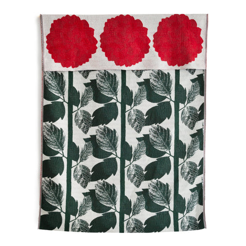 Knit Bloom Blanket that is off white with a dark green, vertical leaf pattern on the front. The blanket is folded over at the top to show a pattern of large red dahlias, three across, on the back side.