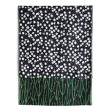 Knit Bloom Blanket that is almost black with a bright green, vertical stem pattern on the front. The blanket is folded over at the top to show a pattern of small, clustered, white baby's breath flowers on the back side.