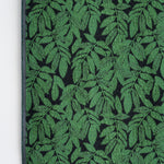 Knit Bloom Blanket reverse side,  with an almost black background showing   a pattern of bright green, clustered leaves.