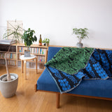 Knit Wisteria Bloom Blanket draped over a couch that has blue upholstery and a wooden frame. The couch is in a room with a concrete planter to the left holding a spindly tree, and a light wooden bookshelf behind it that spans the length of the photo.