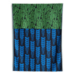 Knit Bloom Blanket that is almost black with a bright blue, vertical wisteria flower pattern on the front. The blanket is folded over at the top to show a pattern of bright green, clustered leaves on the back side.