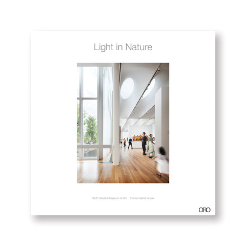 White square book cover with central photograph of a museum gallery with wood floors white walls and ceiling with skylights. Title in gray letters above.