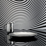 Side view of the creamer and circular dish on a flat, reflective surface, the wall behind them is black and white striped with a funhouse curviness. The Creamer and Dish reflect each other and the striped background.