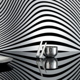 Side view of the sugar bowl with tongs leaning against it, on a flat, reflective surface, the wall behind them is black and white striped with a funhouse curviness. The edge of a dish cuts off on the left side. The dishes reflect each other and the striped background.