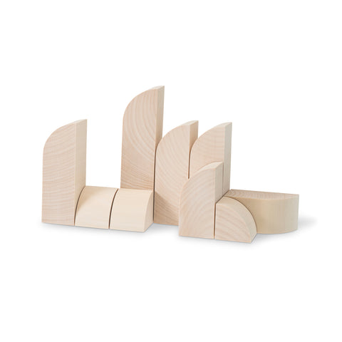 Light colored wooden blocks in a variety of heights standing up against a white background. The blocks are either rectangular with a top end that is rounded on the left and pointed on the right, or small and triangular with one rounded edge.