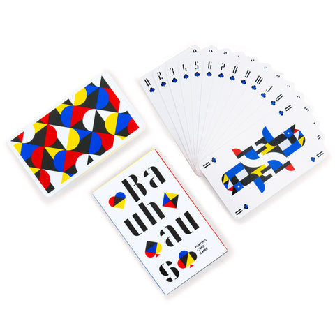 Flat lay of a fanned deck of playing cards, card box, and stack of cards, all featuring geometric graphics in primary colors, on a white background