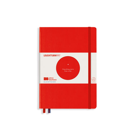 "Bauhaus 100 Notebook A5 in Red. Notebook has rounded corners on the top and bottom right side, a vertical band toward the left, and two ribbon bookmarks peeking out of the bottom right. There is a packaging bellyband with a circle cutout in the center that displays white text printed on the notebook: one dot, with text underneath that says ""Everything starts from a dot."" Bellyband also has text that seys ""Leuchttrum1917"" at the top left and ""100 jahre bauhaus"" on the bottom left."
