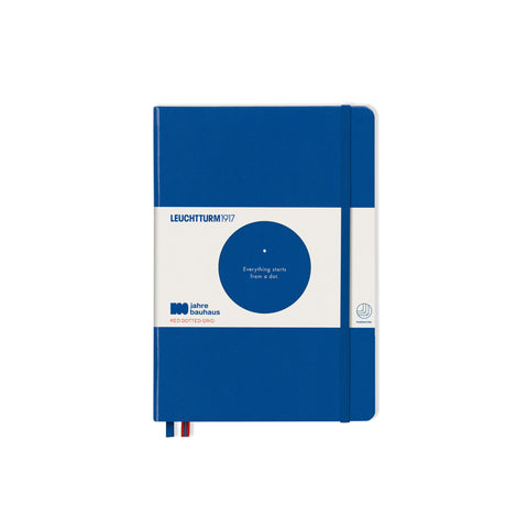 "Bauhaus 100 Notebook A5 in Royal Blue. Notebook has rounded corners on the top and bottom right side, a vertical band toward the left, and two ribbon bookmarks peeking out of the bottom right. There is a packaging bellyband with a circle cutout in the center that displays white text printed on the notebook: one dot, with text underneath that says ""Everything starts from a dot."" Bellyband also has text that seys ""Leuchttrum1917"" at the top left and ""100 jahre bauhaus"" on the bottom left."