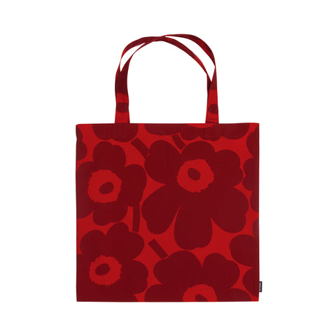Square, standing Pieni Unikko Tote Bag on a white background with two looped carrying handles, a small Marimekko tag bottom right, in an overall pattern of dark red flowers with bright red centers on a bright red background.