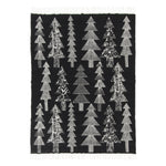 "Black, rectangular blanket with white fringe on a white background, featuring three rows of tall, fanciful spruce trees with stacks of triangular ""foliage"" tiers and trunks filled in with black and white patterns and designs."