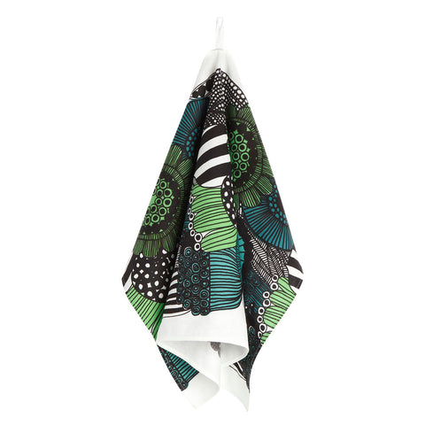 A Pieni Siirtolapuutarha Kitchen Towel is shown hanging from a white cotton tab in triangular folds against a white background, and features a lush floral print, overflowing with brightly-colored, abstract flowers in green, turquoise and teal.