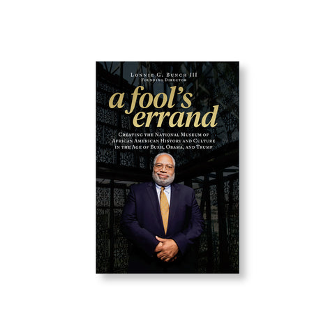 Book cover featuring portrait photo of a white bearded medium dark skin figure in a blue suit with golden yellow tie. Title in lower case golden letters above