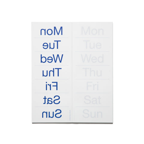 Interior spread of the Weekly Notepad. The right hand side is the same as the cover, with faded gray days of the week, abbreviated at three letters, listed in a stack, with faded blue lines between. The right hand side is the reverse, with backwards text in vibrant, blue indigo.