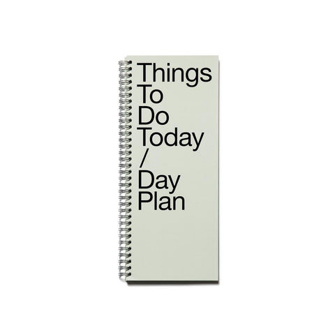 "Tall, narrow notebook with a silver spiral binding. Paper is gray with a hint of green and large, stacked text on the cover reads ""Things To Do Today / Day Plan"""