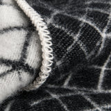 A close-up view of stitch detailing on the border of a black and white blanket