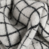 A close-up view of a white blanket with a black geometric grid motif