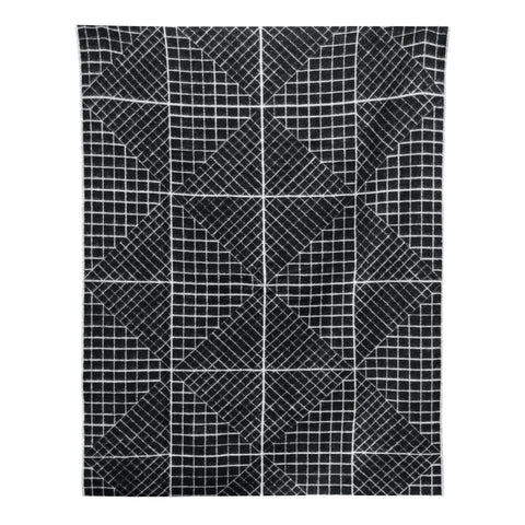 A black and white blanket with a geometric motif