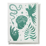 White blanket with green images representing a snake, dove, fern, hand, and Greek god.
