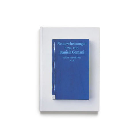 White book cover with photograph of a smaller blue book cover with light blue title near top