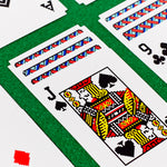 A closeup view of the Susan Kare Solitaire Cards. The cards are spread across a green surface for a game of Solitaire.