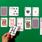 A medium-skinned left hand holds out a playing card. The rest of the deck is spread across a green surface . The hand is playing a game of solitaire.