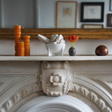 A small matte white standing bowl sits on top of a fireplace mantle with an intricately carved finial. The bowl is filled with white geometric wood pieces and sits next to a trio of orange candles and a small bud vase with a red flower. A gold leaf mirror hangs above the mantle reflecting paintings from across the room.