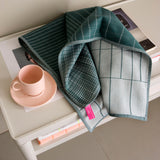 Scholten & Baijings Cold Forest Tea Towel in green atop a white coffee table and placed next to a tea cup and saucer in pink.