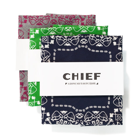 three folded bandanas, one atop the other at an angle. The colors include gray/pink, green/white, and navy blue/white. Each include a graphic print on the border.