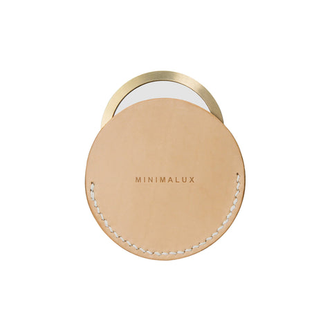 Brass rimmed pocket mirror with a natural leather sleeve. The brand's name is embossed at the center front of the sleeve.