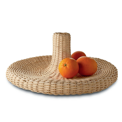 Woven rattan piece holding three oranges shot on white background.
