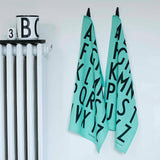 Two light turquoise alphabet tea towels hanging next to each other on a white wall next to a white radiator.