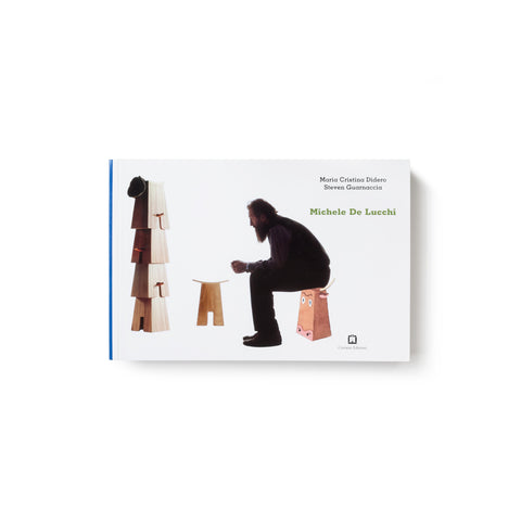 Horizontal white book cover with seated bearded figure in profile surrounded by additional wooden stools, some stacked. The stool being used has a cow face painted on it.