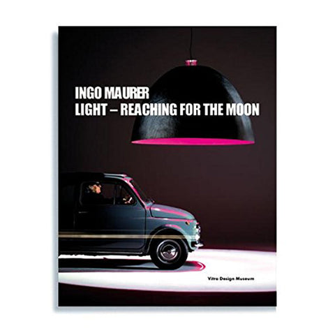Book cover with photograph of a compact blue car under a giant black pendant light emitting magenta light in a dark space. Title in white sans serif letters near top