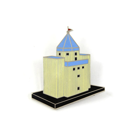 A brooch depicts a yellow building with a blue pointed roof.