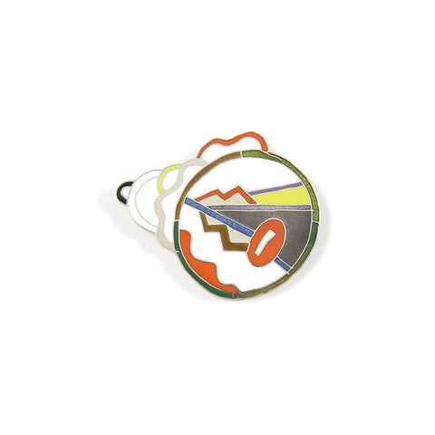 A silver brooch with a colorful abstract circular graphics on the surface.