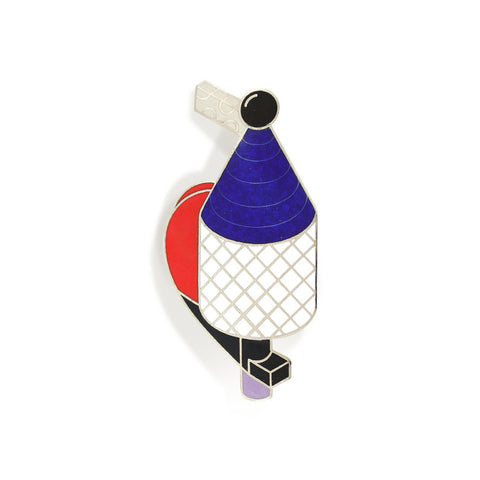 A flat surface of this pin has an abstract combination of geometrical shapes in blue, white, red, and black colores.