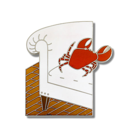 A small pin with an image of a red crab on a white sofa.