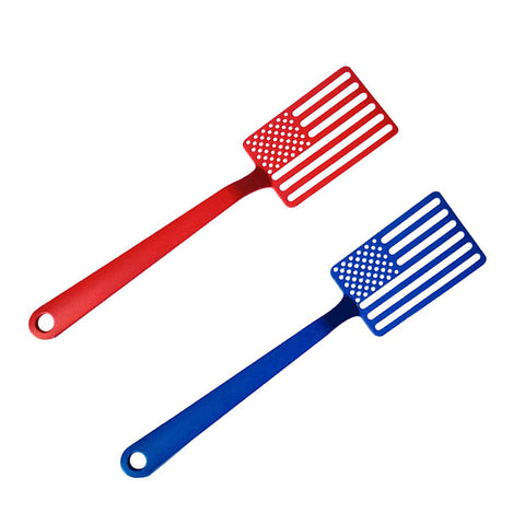 A photograph of a red spatula and a blue spatula laid out on an angle, side by side. They are facing up to show the American flag cutouts that makes up the flipping end of the spatula.