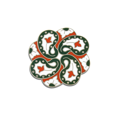 A brooch with a symmetrical pattern with green and red paisley on the white background.