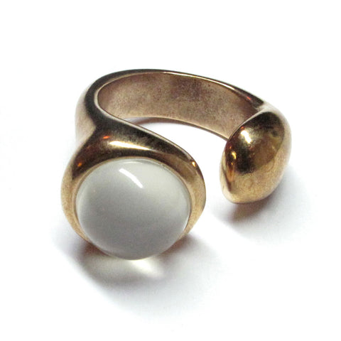A bronze ring with a wide band. A white moonstone is place at the top of the ring. The ring features an opening in its band allowing for more rings to be stacked with this one.